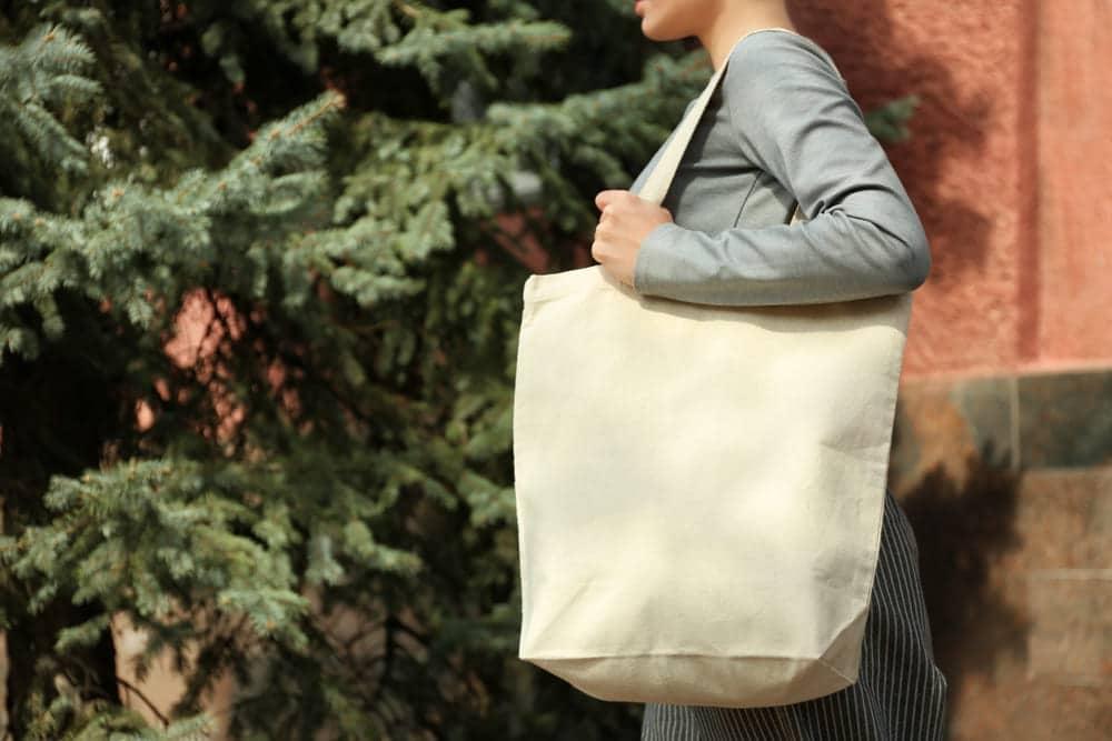 Mulher carregando suas compras em uma sacola ecológica de pano.