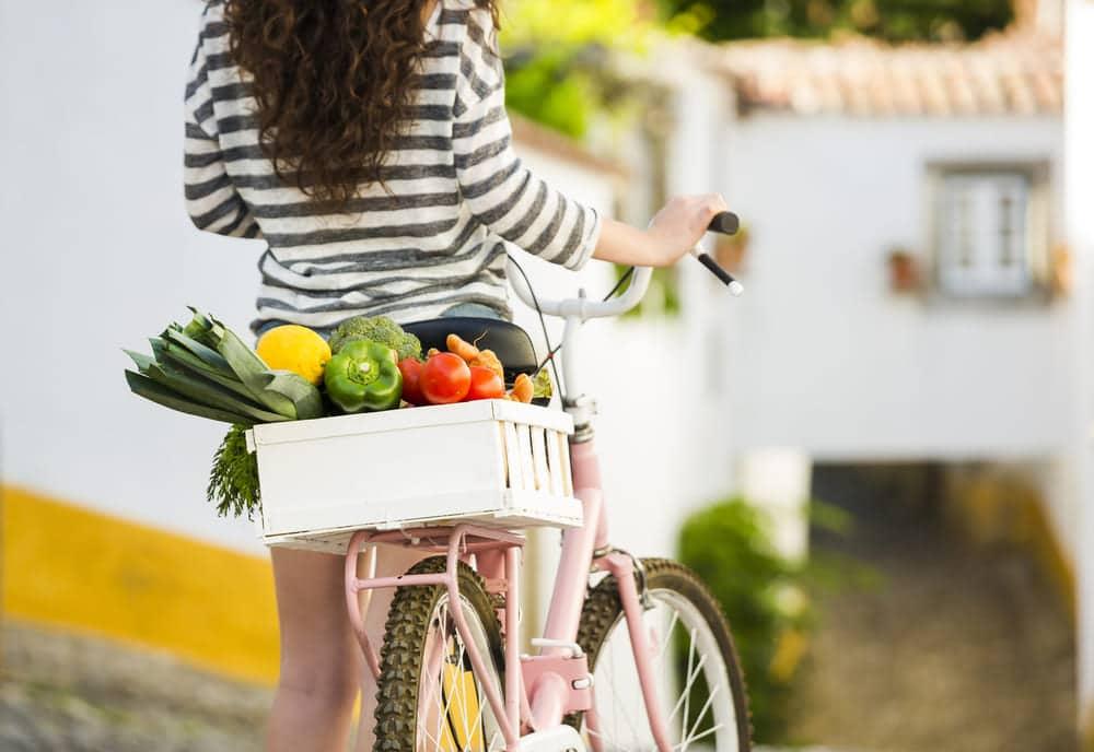 Mulher empurrando bicicleta com compras na cesta traseira.