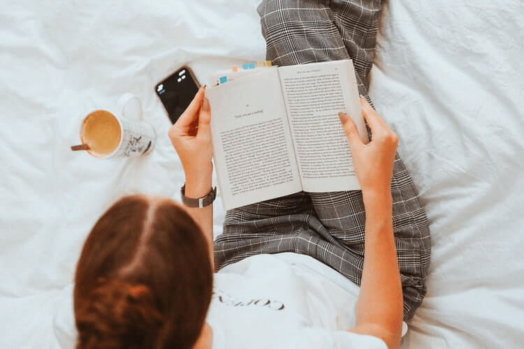 Mulher lendo um livro na cama com uma xícara de café ao lado.