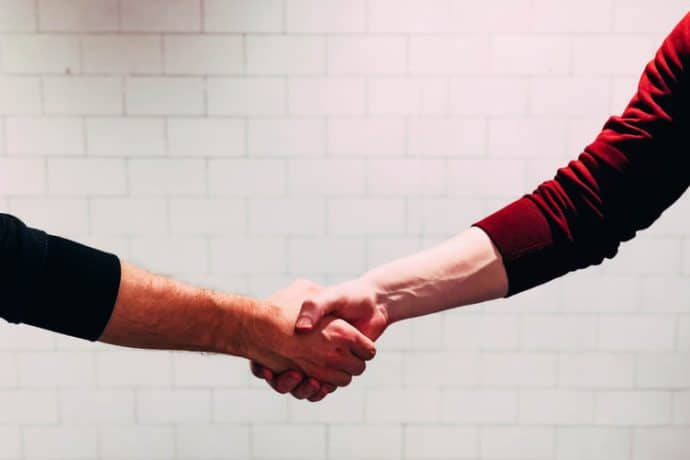 Pessoas dando as mãos uma a outra.