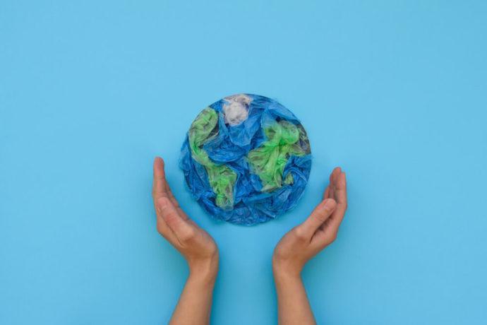 Pessoa com as mãos ao redor de um planeta Terra feito de papel crepom.