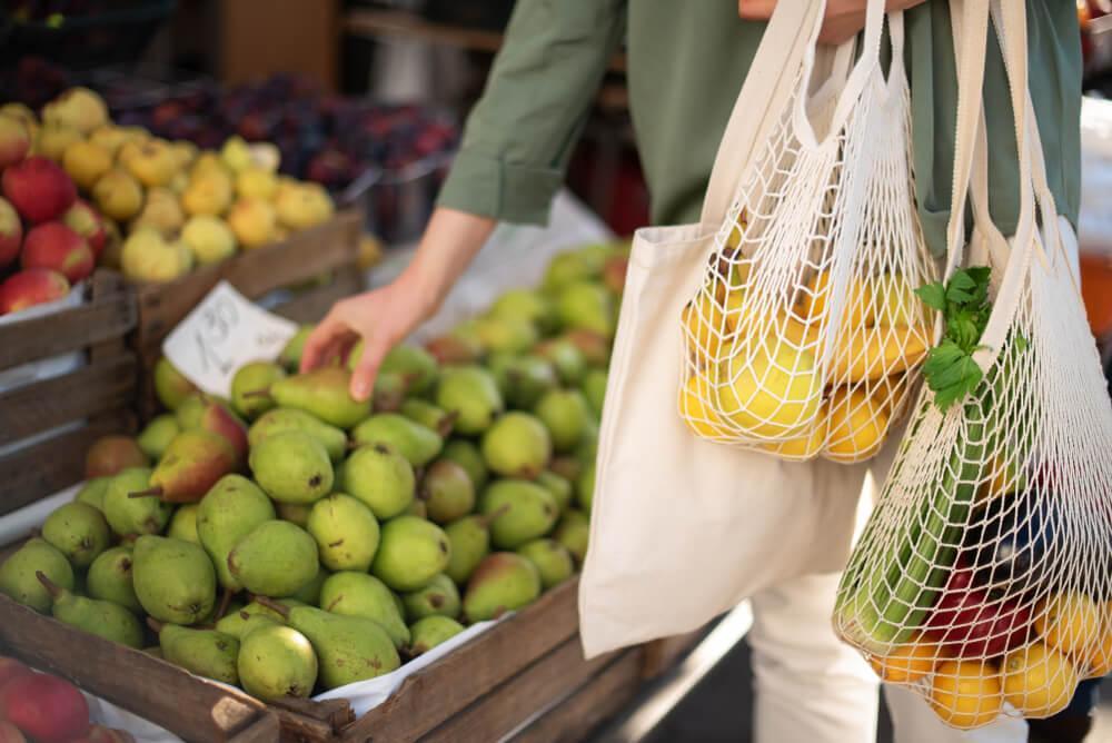 Mulher comprando frutas com sacolas reutilizáveis.