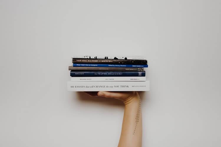M]ao segurando vários livros.