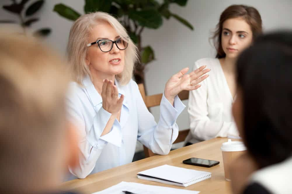 Mulher de cabelos grisalhos e camisa branca conversando em uma mesa com outras.