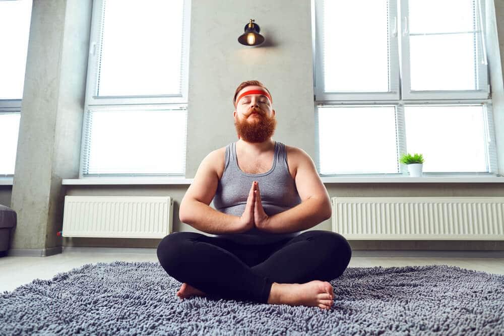 Homem meditando com pernas cruzadas e palma das mãos unidas.