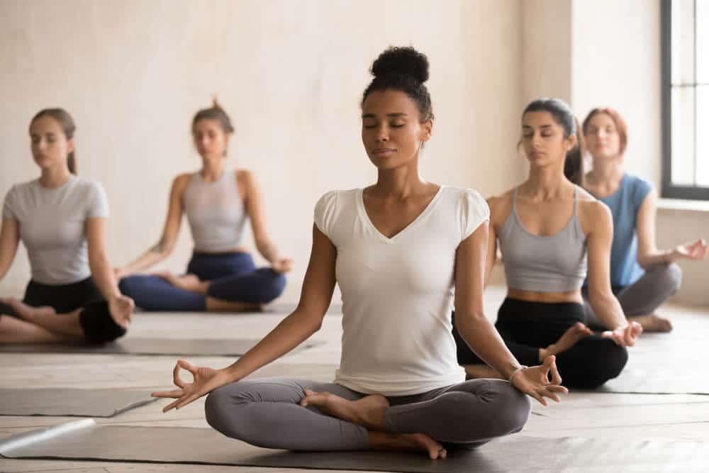 Grupo de mulheres de diferentes etnias reunidas e meditando.