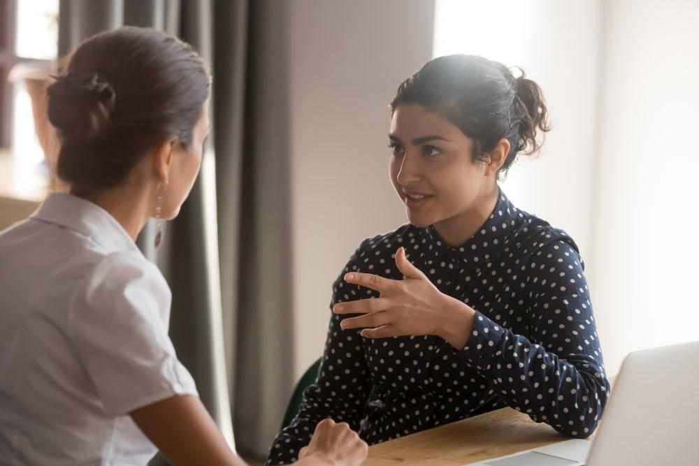 Mulheres conversando com expressão calma e tranqula.