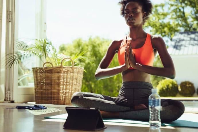 Mulher negra meditando com as mãos juntas e pernas cruzadas.