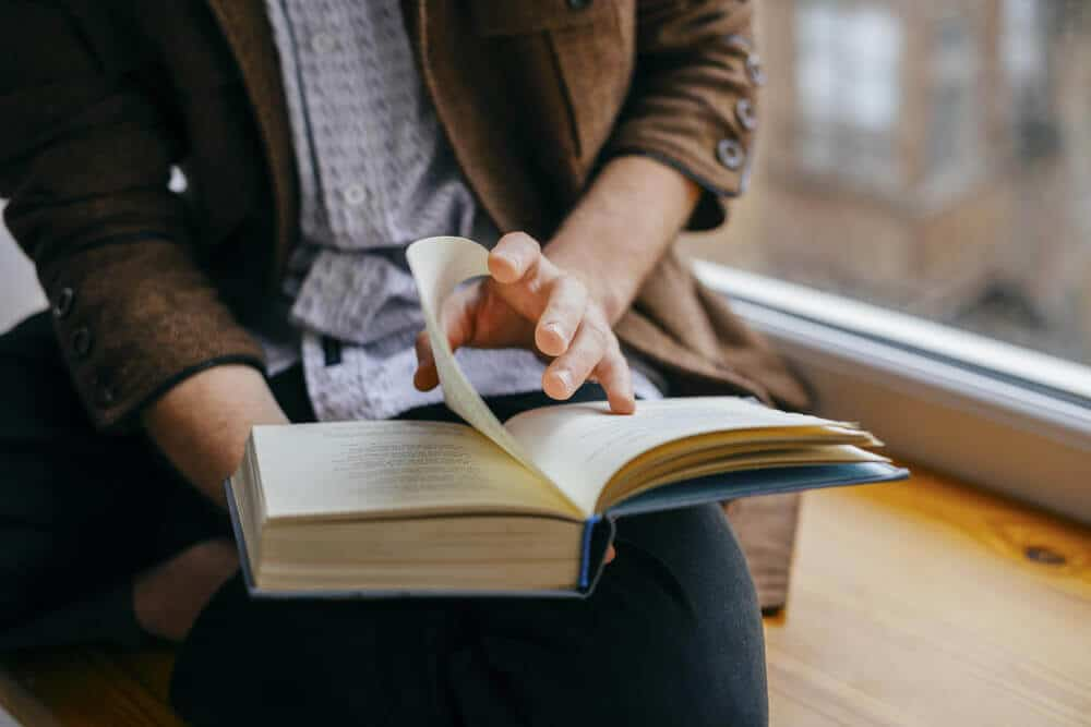 Homem passando a página de um livro com capa azul.