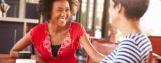 Mulher negra sorrindo enquanto conversa com sua amiga.