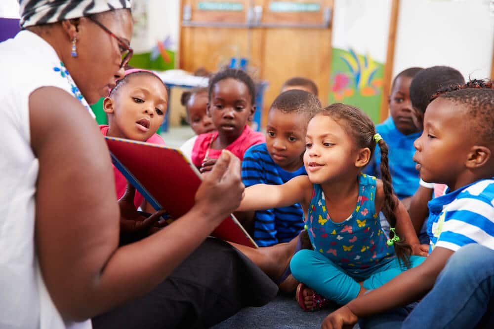 Professora lendo para um grupo com diversas crianças negras.