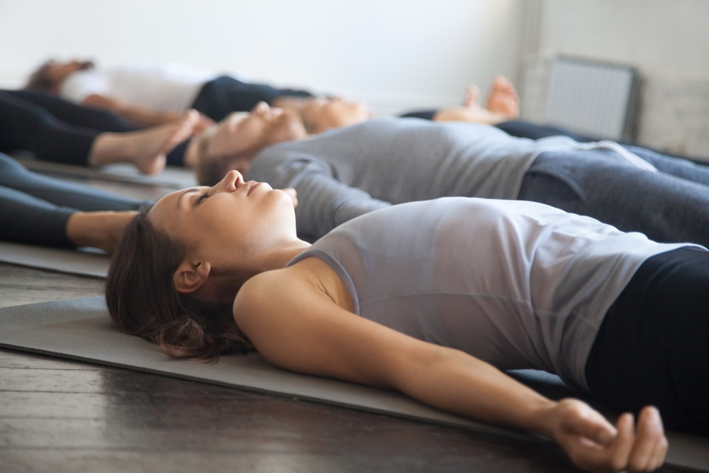 Mulher meditando deitada e com os braços encostados ao chão.