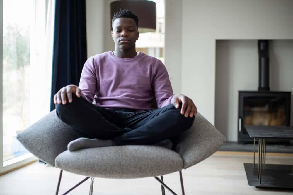 Garoto negro sentado em uma poltrona, com as pernas cruzadas, meditando.
