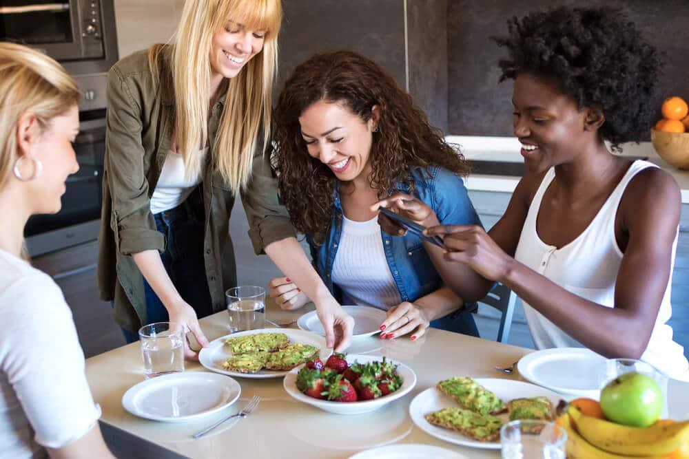 Amigas lanchando juntas, com pratos de frutas e de lanches com pasta de abacate na mesa.