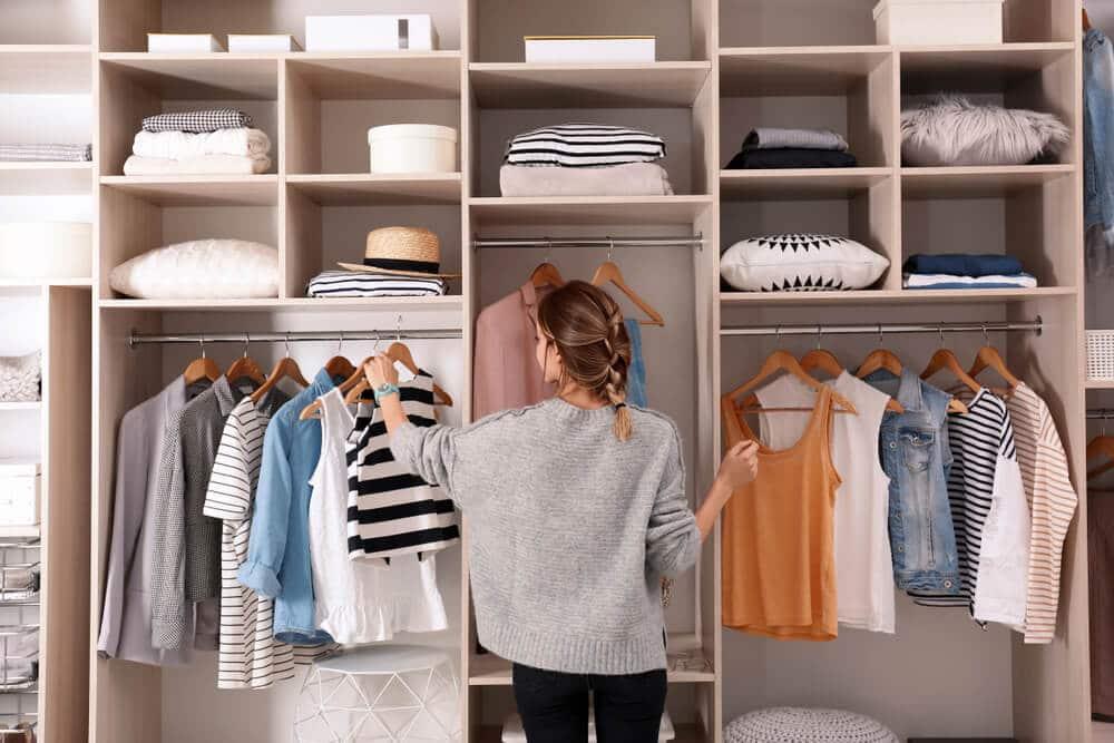 Mulher organizando o guarda-roupa e separando peças para doar.