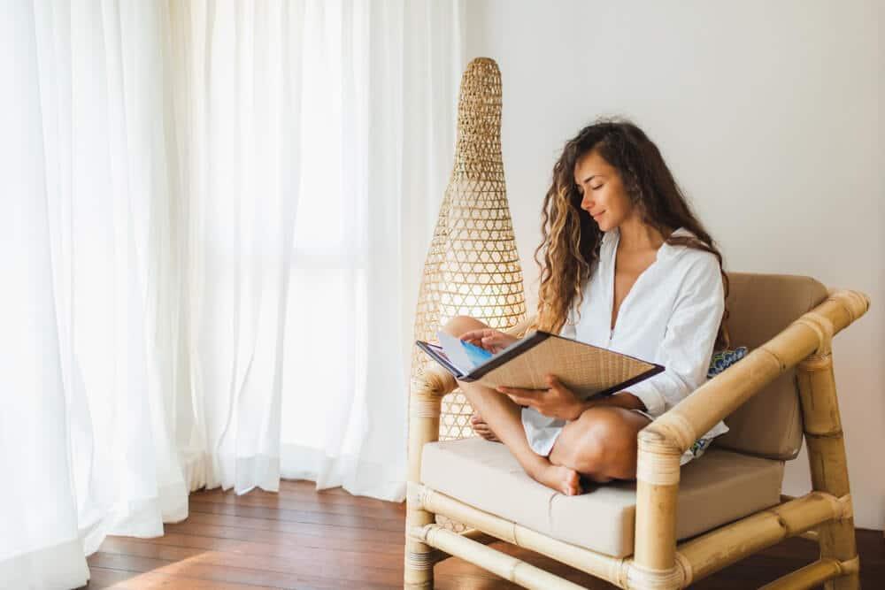 Mulher lendo e sentada em uma cadeira em um ambiente minimalista.