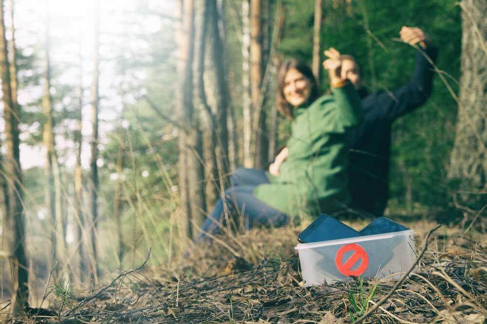 Um homem e uma mulher na natureza com os celulares depositados em pote com símbolo de proibido.