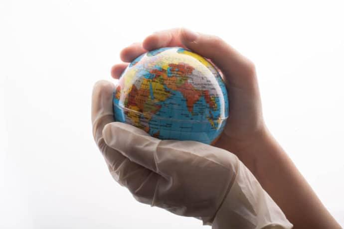 Mãos com luva segurando um globo terrestre.