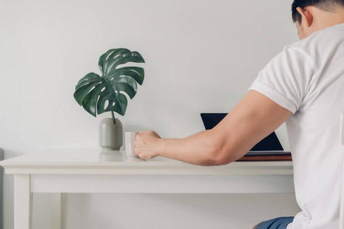 Homem sentado à mesa minimalista com uma planta, um computador e uma caneca de café.