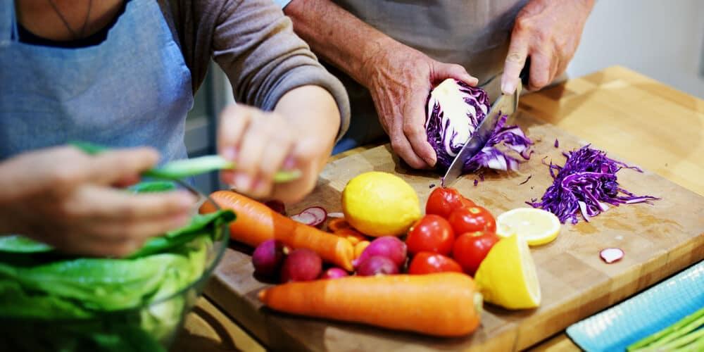 Mãos cortando legumes sobre uma tábua de madeira.