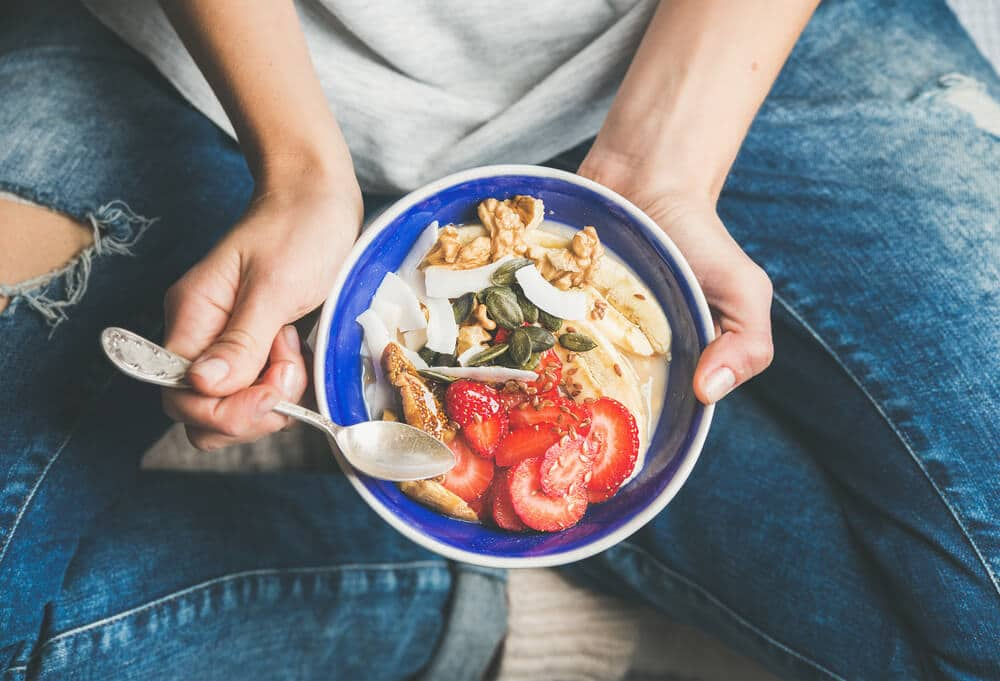 Pessoa segurando um pote com frutas, iogurte e castanhas.