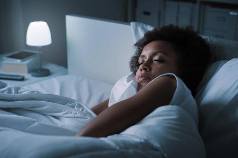 Mulher negra dormindo com abajur aceso ao lado.