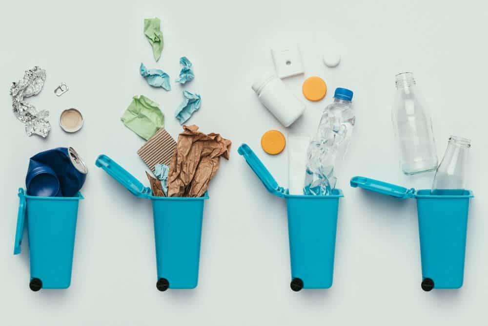 Resíduos diferentes sendo descartados em seus devidos lixos.